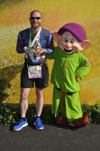 Josh Zeigler presenting his medals with Dopey after the Dopey Challenge at the 2018 Walt Disney World Marathon Weekend